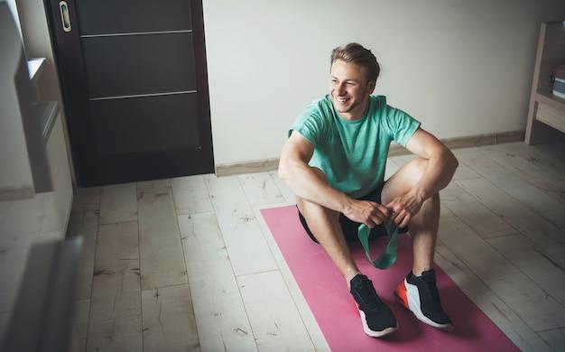 Glimlachende man met blonde haren, het dragen van sportkleding op de vloer tijdens een fitnessles thuis