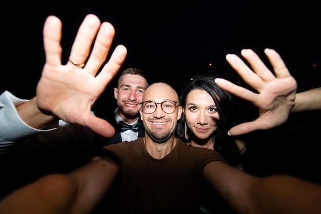 Glimlachende man met bruidspaar selfie te nemen 's nachts
