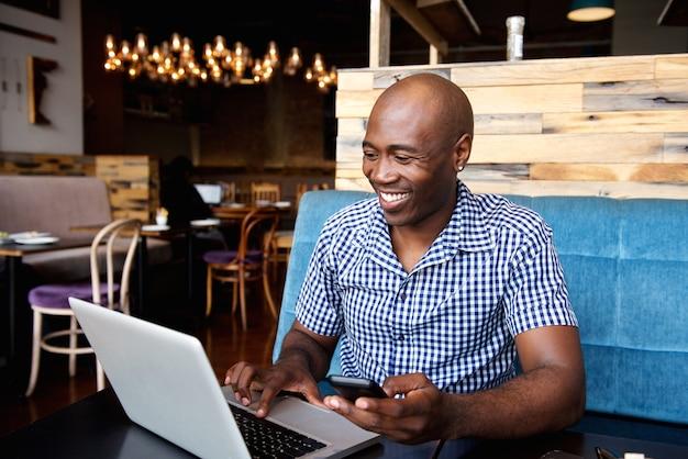 Glimlachende man met een mobiele telefoon zit op café met behulp van de laptop