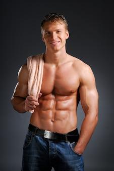 Glimlachende man met een sterk en sexy lichaam dat de handdoek vasthoudt