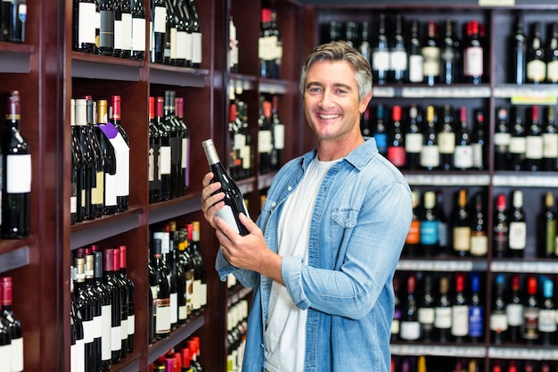 Glimlachende man met fles wijn