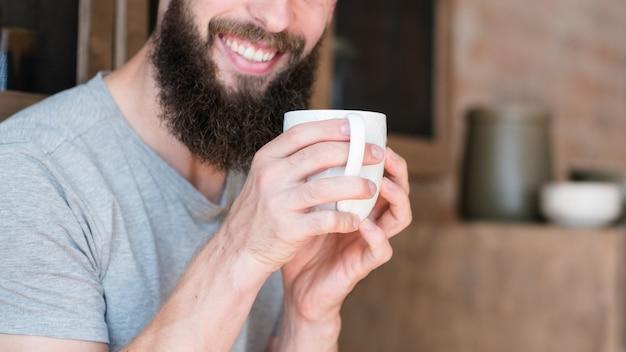 Glimlachende man met kop warme drank. wakker worden en de dag plannen.