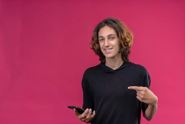 Glimlachende man met lang haar in zwart t-shirt die een telefoon vasthoudt en op roze muur wijst