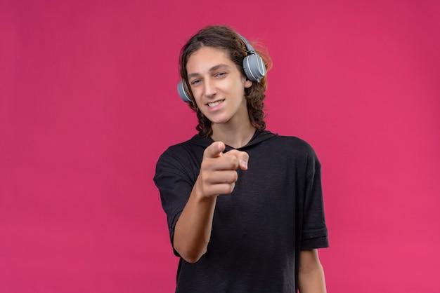 Glimlachende man met lang haar in zwart t-shirt luistert naar muziek uit de koptelefoon en wijst naar voren op de roze muur