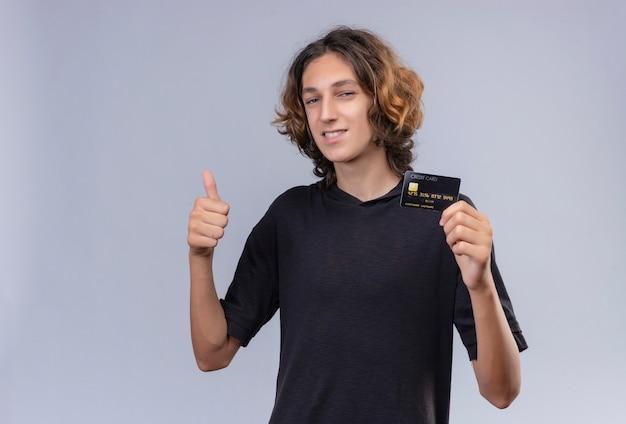 Glimlachende man met lang haar in zwart t-shirt met een bankkaart en opgeheven duim op witte muur