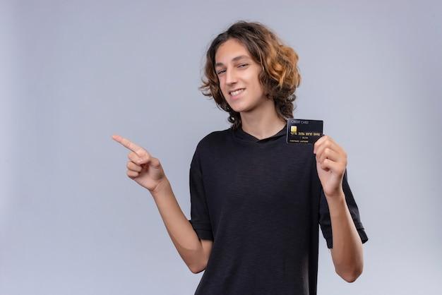 Glimlachende man met lang haar in zwart t-shirt met een bankkaart en wijst naar de andere kant op witte muur