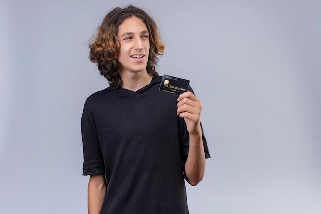 Glimlachende man met lang haar in zwart t-shirt met een bankkaart op een witte muur