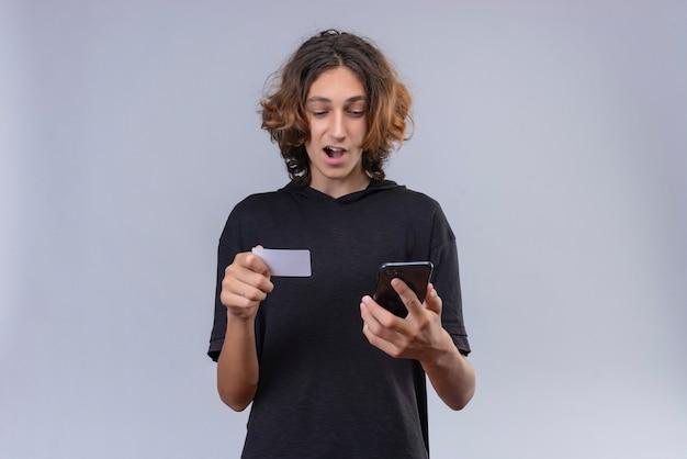 Glimlachende man met lang haar in zwart t-shirt met een telefoon en bankkaart op witte muur