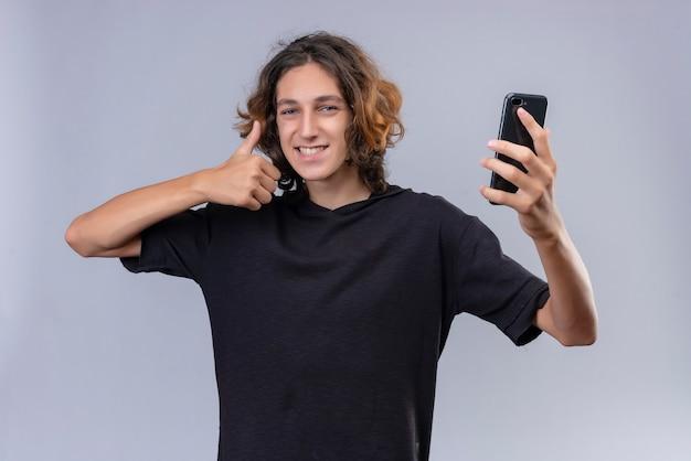Glimlachende man met lang haar in zwart t-shirt met een telefoon en duim opdagen op witte muur