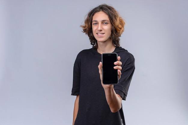 Glimlachende man met lang haar in zwart t-shirt met een telefoon op een witte muur