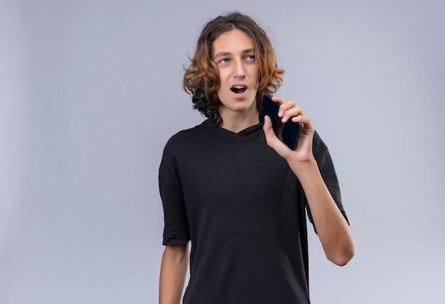 Glimlachende man met lang haar in zwart t-shirt spreken aan de telefoon via de luidspreker op de witte muur