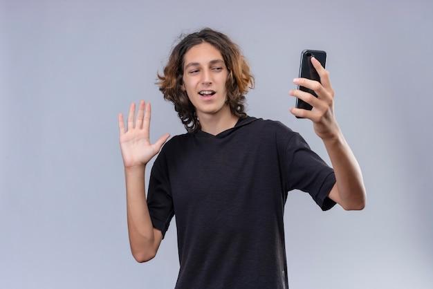 Glimlachende man met lang haar in zwarte t-shirt die op telefoon op witte muur spreekt