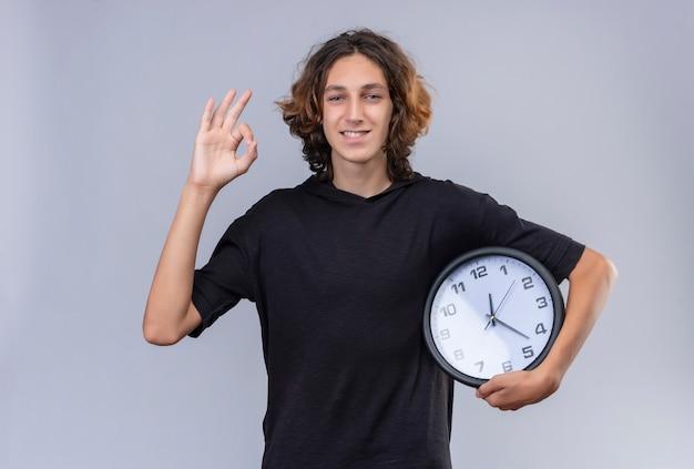 Glimlachende man met lang haar in zwarte t-shirt met een wandklok en toont ok gebaar op witte muur