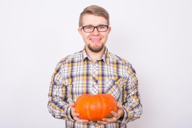 Glimlachende man met pompoenen op witte achtergrond