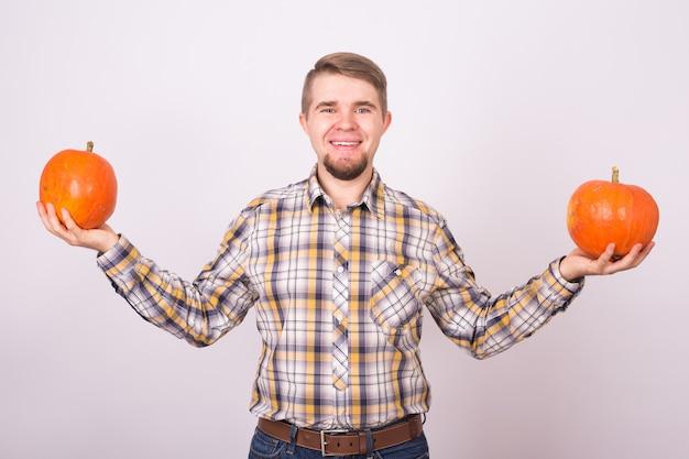 Glimlachende man met pompoenen over witte achtergrond oogst en herfst concept