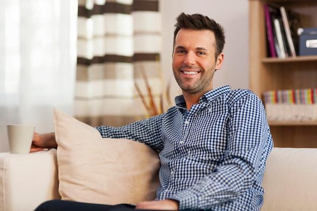 Glimlachende man met reinigingsapparatuur in de woonkamer