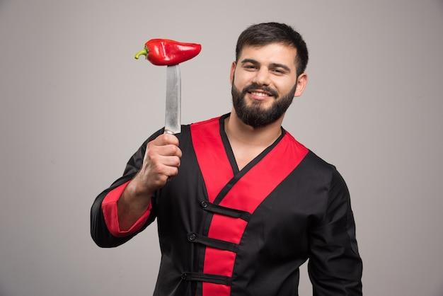 Glimlachende man met rode peper op mes.