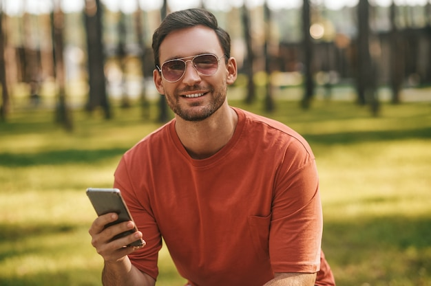 Glimlachende man met smartphone camera kijken