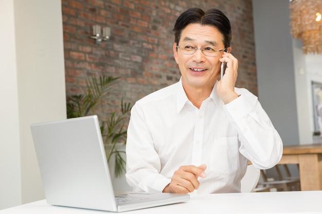 Glimlachende man op een telefoongesprek in de woonkamer