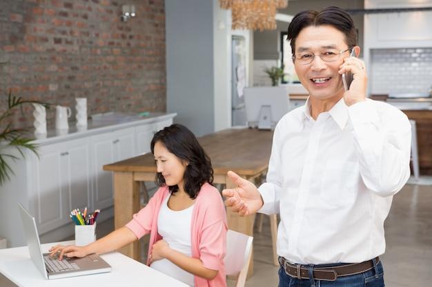 Glimlachende man op een telefoongesprek terwijl de zwangere vrouw laptop gebruikt