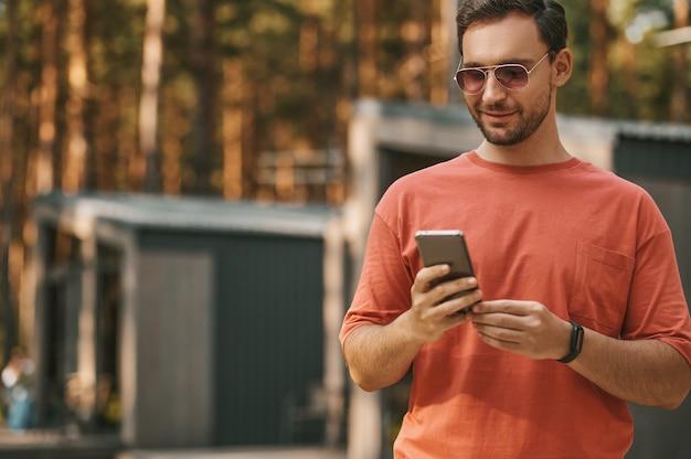 Glimlachende man op zoek naar smartphone buitenshuis