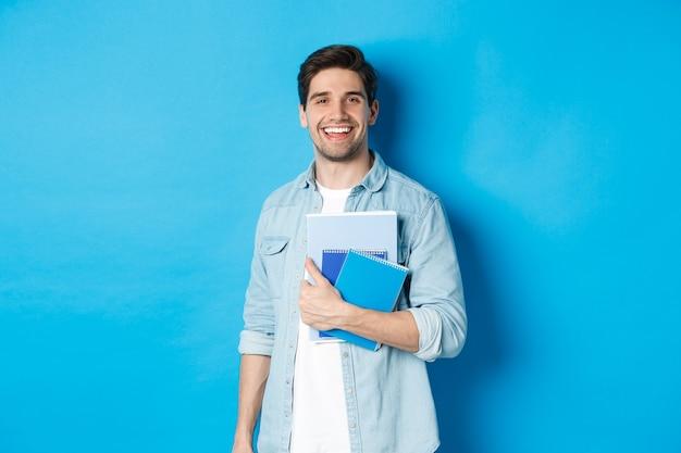 Glimlachende man studeert, houdt notitieboekjes vast en ziet er gelukkig uit, staande over een blauwe achtergrond