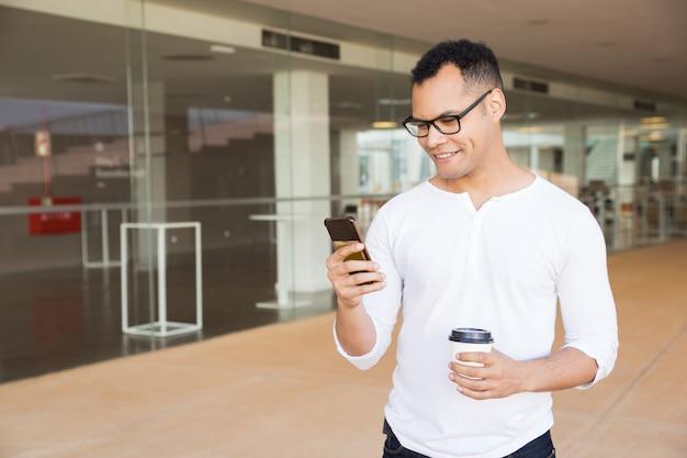Glimlachende man texting op telefoon, afhaalmaaltijden koffie te houden