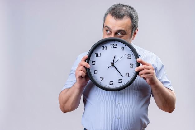 Glimlachende man van middelbare leeftijd die blauwe verticale gestripte de muurklok van de overhemdsholding dragen die tijd toont terwijl hij op een witte achtergrond staat
