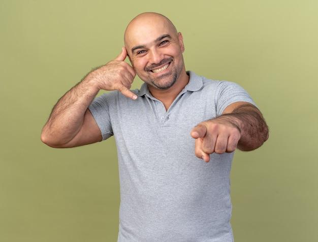 Glimlachende man van middelbare leeftijd die een oproepgebaar doet en naar de voorkant wijst, geïsoleerd op een olijfgroene muur