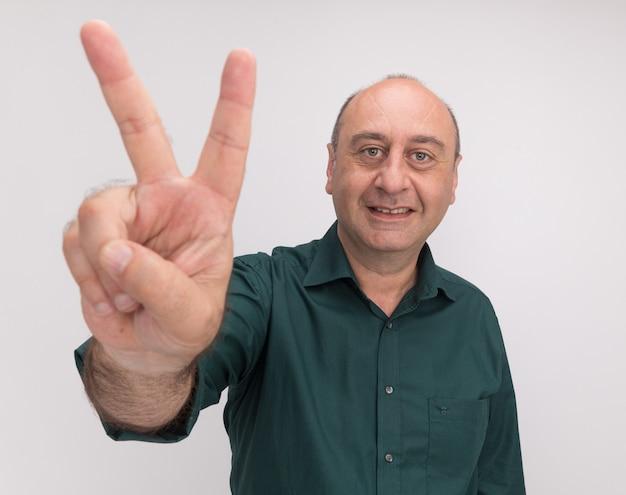 Glimlachende man van middelbare leeftijd die groen t-shirt draagt dat vredesgebaar toont dat op witte muur wordt geïsoleerd