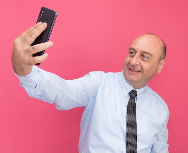 Glimlachende man van middelbare leeftijd met een wit t-shirt met stropdas neemt een selfie geïsoleerd op een roze muur