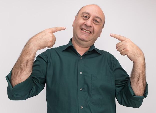 Glimlachende man van middelbare leeftijd met groene t-shirt wijst naar zichzelf geïsoleerd op een witte muur