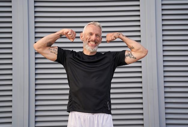 Glimlachende man van middelbare leeftijd stak zijn armen omhoog en laat zijn biceps zien terwijl hij buiten over grijs poseert