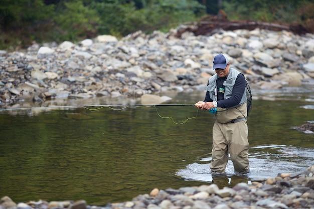 Glimlachende man wandelen in de rivier in waterdichte kleding en vissen met rob. gelukkig visser in pet en zonnebril genieten van favoriete sportactiviteit in de frisse lucht.