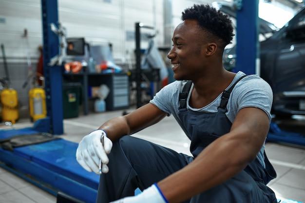 Glimlachende man werknemer zittend op autolift in mechanische werkplaats