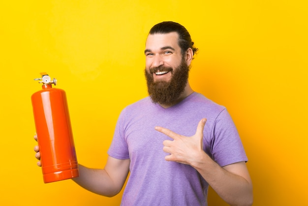 Glimlachende man wijst naar een rode brandblusser over gele achtergrond.