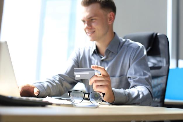 Glimlachende man zit op kantoor en betaalt met een creditcard met zijn laptop.