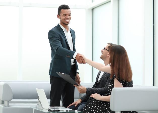 Glimlachende manager begroet klanten in de lobby van het kantoor. foto met kopieerruimte