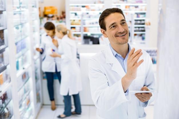 Glimlachende mannelijke apotheker in witte kleren met een tablet in zijn hand die zich bij de apotheek bevindt, vrouwelijke collega's op afstand