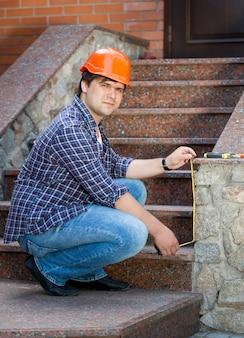 Glimlachende mannelijke arbeider die stenen trap meet met meetlint