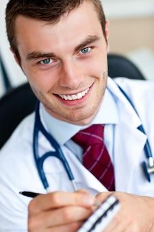 Glimlachende mannelijke arts die een perscription schrijft
