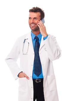 Glimlachende mannelijke arts die op mobiele telefoon spreekt
