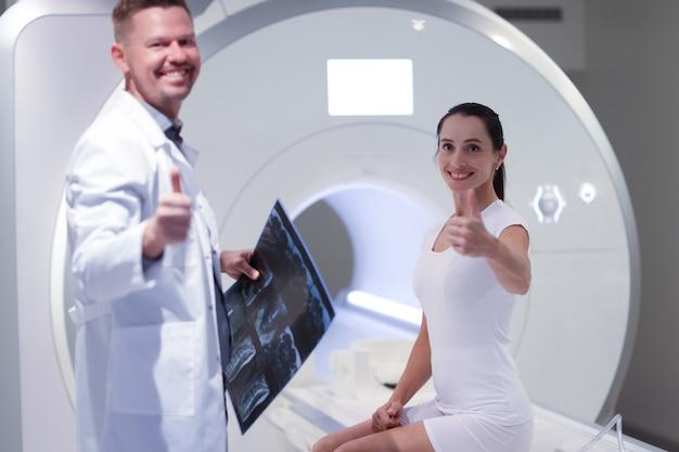 Glimlachende mannelijke arts en vrouwelijke patiënt houden duimen omhoog in kantoor voor medisch mri-onderzoek