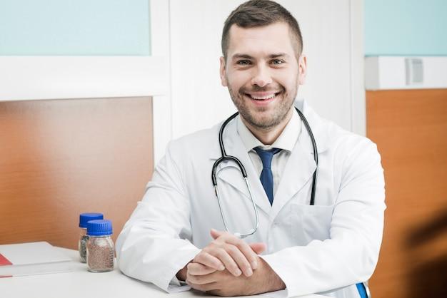 Glimlachende mannelijke arts in kliniek