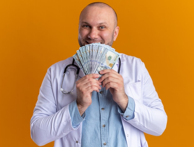 Glimlachende mannelijke arts van middelbare leeftijd met een medisch gewaad en een stethoscoop die geld vasthoudt op een oranje muur