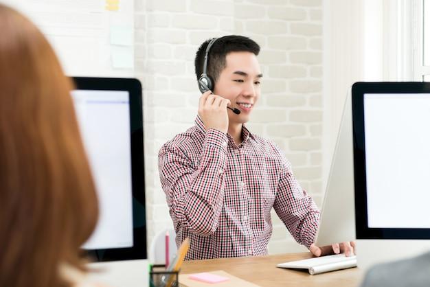 Glimlachende mannelijke aziatische telemarketingsagent in call centre