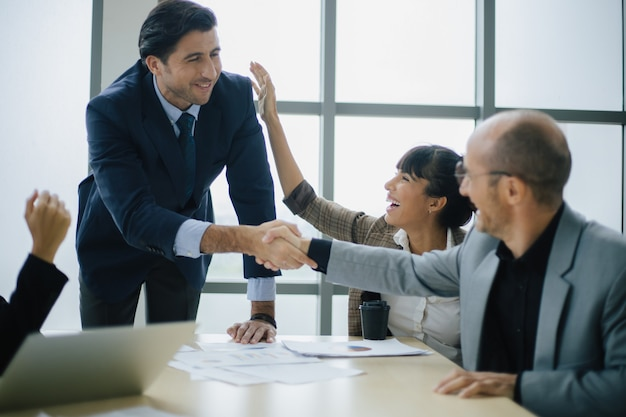 Glimlachende mannelijke baas in gesprek met business team business. technologie en kantoorconcept.