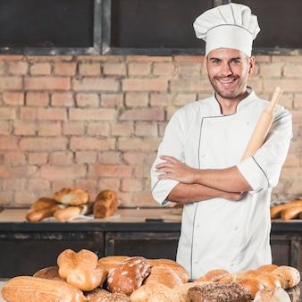 Glimlachende mannelijke bakker met verschillend type gebakken broden in bakkerij