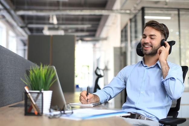 Glimlachende mannelijke bedrijfsadviseur met koptelefoon zittend op modern kantoor, videogesprek kijkend naar laptopscherm. man klantenservice ondersteuning agent hulplijn praten online chat.