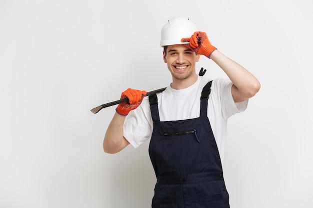 Glimlachende mannelijke bouwer die in beschermende helm en handschoenen koevoet houdt terwijl over grijze muur